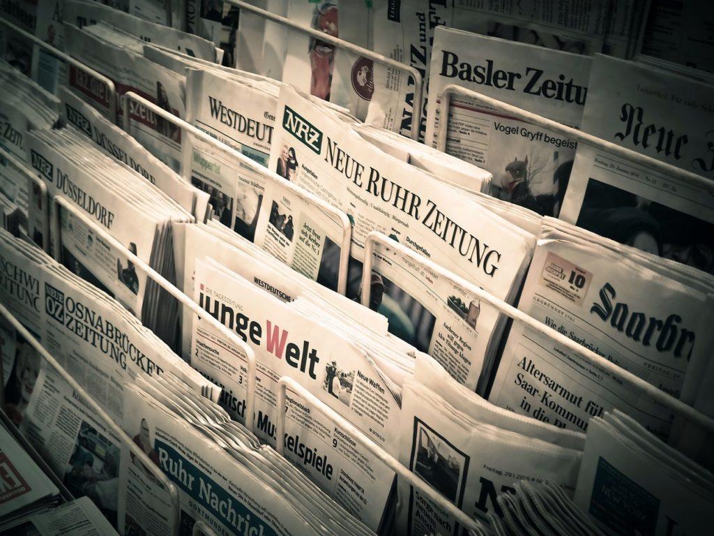 Tageszeitungen in einem Zeitungsständer. Mit einer guten Pressemitteilung ist eine Veröffentlichung wahrscheinlicher.